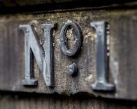 Tecken för gataadress Nummer 1 Nummer ett… Arkivbild