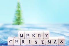 Tecken för glad jul som göras av träbokstäver Arkivbild