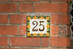 Tecken för husnummer 25 på den målade väggen i keramiska tegelplattor och Royaltyfri Foto