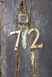 Tecken för husnummer 72 på träportstolpen Arkivbild