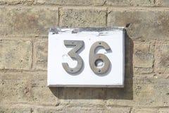 Tecken för husnummer 36 på väggen Arkivbild