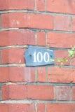 Tecken för husnummer 100 på väggen Royaltyfri Foto