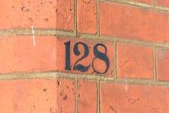 Tecken för husnummer som 128 målas på väggen Royaltyfri Bild