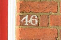 Tecken för husnummer som 46 målas på väggen Arkivbilder