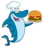 Tecken för kockBlue Shark Cartoon maskot som rymmer en stor hamburgare stock illustrationer