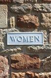 Tecken för kvinnatoalettbadrum på tegelstenväggen Royaltyfri Fotografi
