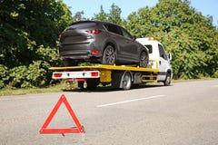 Tecken för nöd- stopp med den brutna bilen och bärgningsbilen royaltyfri fotografi
