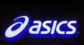 Tecken för neon för Asics logoblått Asics är ett japanskt multinationellt företag som producerar skodon- och sportutrustning Royaltyfria Foton
