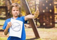 Tecken för pennalism för ledsen pojkeholdingn anti-mot lekplats fotografering för bildbyråer