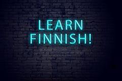 Tecken för tegelstenvägg och neonmed inskriften Begrepp av att lära finska arkivbilder