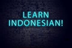 Tecken för tegelstenvägg och neonmed inskriften Begrepp av att lära indones arkivfoto