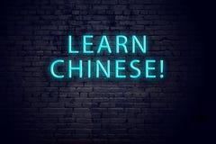 Tecken för tegelstenvägg och neonmed inskriften Begrepp av att lära kines royaltyfri fotografi