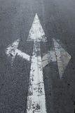 Tecken för tre pilar på asfaltvägen Arkivfoton
