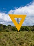 Tecken för triangel för sändningsnavigeringguling på land Arkivfoton