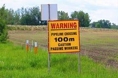 Tecken för varningsrörledningkorsning varning arkivfoton