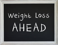 Tecken för viktförlust på svart kritabräde royaltyfri fotografi
