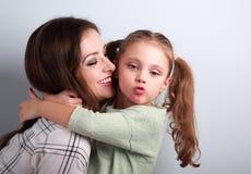 Tecken för kyss för visning för flicka för gyckelöversittareunge med moderläppstiftkyss M Fotografering för Bildbyråer