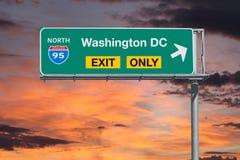 Tecken för motorväg för Washington DCutgång endast med soluppgånghimmel Arkivfoton