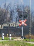 Tecken med drevuppsättningen på den järnväg korsningen Arkivfoton