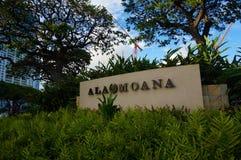 Tecken med namnet av gallerian 'alun Moana 'i gräset under blå himmel och träd i den Hawaii ön Oahu royaltyfria foton