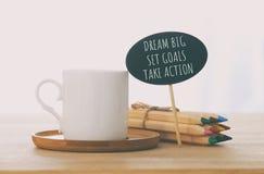 tecken med text: DRÖM- STORT, STÄLLDE IN MÅL, TAR HANDLING bredvid koppen kaffe över trätabellen arkivbilder
