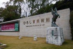 Tecken och pegasus staty framme av den Hiroshima konstmuseet Arkivfoto