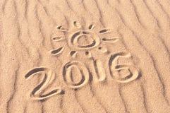 Tecken 2016 och sol som är skriftlig på den sandiga stranden Sommarloppbegrepp Arkivfoton