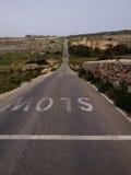Tecken som är långsamt på en lång väg Royaltyfri Fotografi