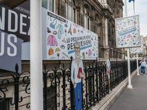 Tecken som annonserar klädutställningen utanför Hotell de Ville, rue D Arkivfoton