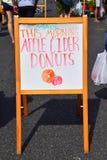 Tecken som annonserar nya äppelciderdonuts med den utdragna bilden av ett äpple och en munk arkivfoton