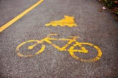 Tecken som cyklar, och inline åka skridskor spår på asfalten Royaltyfri Fotografi