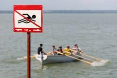 Tecken som förbjuder simning i detta ställe på bakgrunden av en träeka med folk royaltyfria foton
