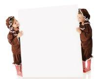 Tecken som flankeras av Pepparkaka Flicka Royaltyfria Bilder
