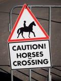 Tecken som hänger på porten med bilden av hästryttaren och ord VARNING! KORSA FÖR HÄSTAR royaltyfri fotografi