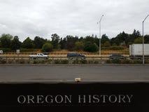 Tecken som säger Oregon historia på sida av vägen med bilar arkivbild