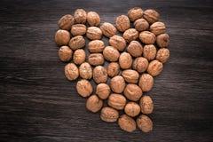 Teckenhjärta som fodras med rå valnötter på träbakgrund Valnöthjärtaform arkivbild