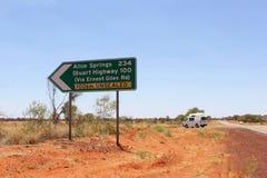 Teckenstolpe av en oförseglad väg till Alice Springs, Australien Arkivbilder