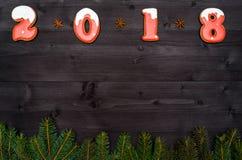 Teckensymbol för lyckligt nytt år 2018 från röda och vita pepparkakakakor på mörk träbakgrund med granträdfilialer royaltyfria bilder