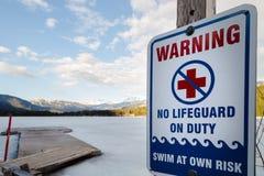 Teckenvarning att det inte finns någon livräddare som är tjänstgörande på nära en djupfryst vintersjö royaltyfri bild
