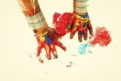 Teckna förbi handen Barnhänder målade i färgrika målarfärger på vit bakgrund royaltyfri fotografi