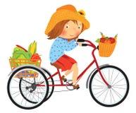 Tecknad filmbondeflicka på en cykel med frukter Royaltyfria Bilder