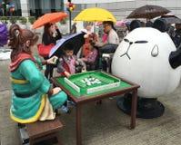 Tecknad filmskulpturer spelar mahjong nära återföreningmonumentet, Royaltyfri Foto