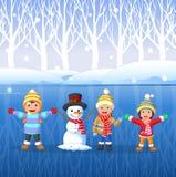 Tecknad filmungar som spelar på insnöad vintertid Arkivfoto