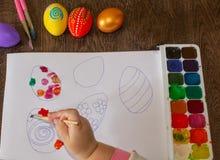 tecknar flickan Barns teckning för påsken, målningägg royaltyfri foto