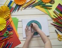 tecknar flickan Kreativitet för barn` s Favorit- hobby för barn Material och hjälpmedel Barnet ligger på golvet och drana royaltyfria bilder