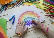 tecknar flickan Kreativitet för barn` s Favorit- hobby för barn Material och hjälpmedel Barnet ligger på golvet och drana arkivfoton