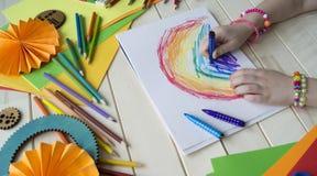 tecknar flickan Kreativitet för barn` s Favorit- hobby för barn Material och hjälpmedel Barnet ligger på golvet och drana arkivbild