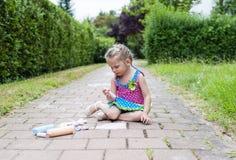 tecknar konkreta teckningar för asfaltkritachld flickalinjen målningsmålningar som vägen sitter fyrkanten Barnteckningsmålningar  royaltyfri foto