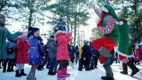 Tecknare spelar med barnen, julberömmar i staden, pojkar, och flickor spelar med älvorna på en vinter arkivfilmer