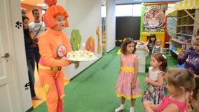 Tecknaren ger kakan med stearinljus för födelsedag En ferie i klubba för barn` s arkivfilmer